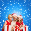 Smiling family holding gift boxes and sparkles — Stock Photo