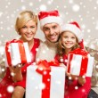 Smiling family giving many gift boxes — Stockfoto
