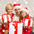 Smiling family giving many gift boxes — Стоковое фото