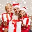 Smiling family giving many gift boxes — ストック写真
