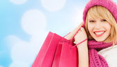 Woman in pink hat and scarf with shopping bags — Stock fotografie