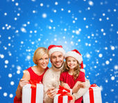 Smiling family holding gift boxes and sparkles — 图库照片