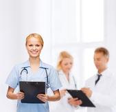 面带笑容的女医生或护士与剪贴板 — 图库照片
