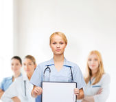 Smiling female doctor or nurse with sclipboard — Stockfoto