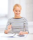 Woman with notebook and calculator studying — Stock Photo