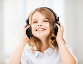 Smiling little girl with headphones at home — Stock fotografie