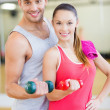 Two smiling people working out with dumbbells — Stock fotografie