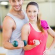 Two smiling people working out with dumbbells — Stock Photo