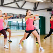 Stock Photo: Group of smiling people exercising in the gym