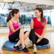 Two smiling women sitting on the half balls — Stock Photo