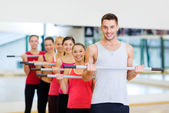 Group of smiling people working out with barbells — Stock fotografie