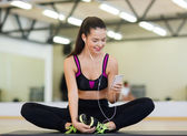 Smiling woman stretching on mat in the gym — Stok fotoğraf
