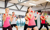 Group of smiling people working out with dumbbells — Stok fotoğraf