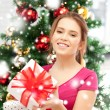 Happy woman with gift boxes and christmas tree — Photo