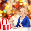 Woman with gifts, laptop computer and credit card — Stock Photo #36196561