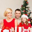 Smiling family holding many gift boxes — Stock Photo