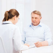 Female doctor or nurse with old man prescrbing — Stockfoto