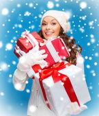 Kvinna i tröja och mössa med många presentförpackning — Stockfoto