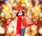 Smiling woman in warm clothers with shopping bags — Stock fotografie