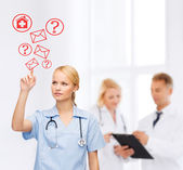 Focused doctor or nurse pointing to red envelope — Stockfoto