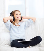 Girl with tablet pc and headphones at home — Stock Photo