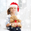 Smiling girl in santa helper hat with teddy bear — Photo