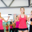 Group of smiling people working out with barbells — Stok fotoğraf