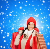 Smiling woman in warm clothers with shopping bags — Stock Photo