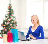 Woman with laptop, shopping bags and credit card — Stock Photo