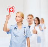 Smiling doctor or nurse pointing to hospital icon — Stockfoto