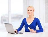 Smiling woman with laptop computer and credit card — Stock Photo