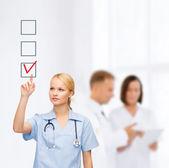 面带笑容的医生或护士指向选中标记 — 图库照片