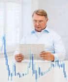 Old man at home with newspaper and forex chart — Stock Photo