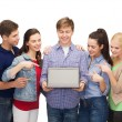 Smiling students with laptop computer — Foto Stock