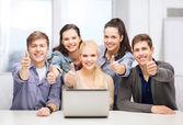 Başparmak gösterilen laptop ile gülümseyen öğrenciler — Stok fotoğraf