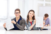 Two teenagers holding test or exam with grade A — Stock Photo