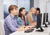 Students looking at computer monitor at school — Stock Photo