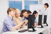Students with computer monitor and smartphones — Stock Photo
