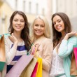 Three smiling girls with shopping bags in ctiy — Stock Photo