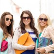 Three smiling women with bags in the city — Stock Photo