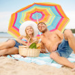 Smiling couple sunbathing on the beach — Stock Photo