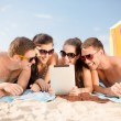 Group of smiling people with tablet pc on beach — Stock Photo