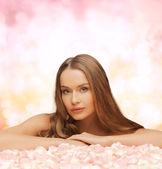 Woman with long hair and rose petals — Stockfoto