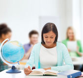 Teacher with globe and book at school — Stock Photo