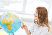 Smiling student girl with globe at school — Stock Photo