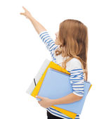 Little student girl with notebooks pointing to — Stock Photo
