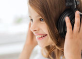 Smiling little girl with headphones at home — Stock Photo