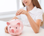 Smiling child putting coin into big piggy bank — Stock Photo