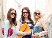 Tres mujeres sonrientes con bolsas en la ciudad — Foto de Stock