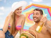 Smiling couple having picnic on the beach — Stock Photo